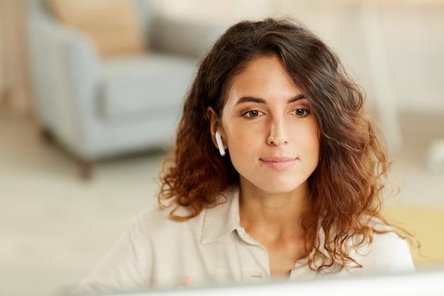 집에서 컴퓨터에서 작업하는 젊은 성인 백인 사업가의 수평 중간 클로즈업 초상화