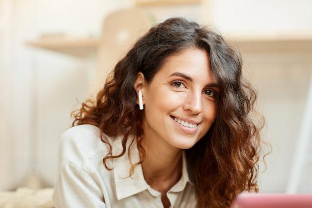 아름다운 곱슬 머리를 가진 젊은 성인 여자의 수평 중간 클로즈업 초상화