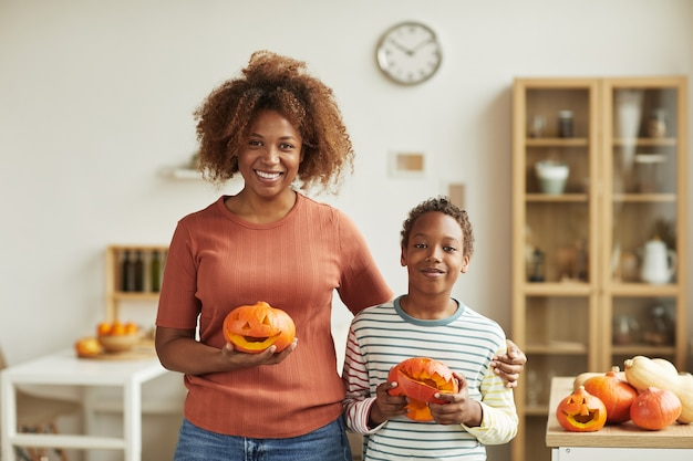 Horizontal medium portrait of young adult woman and her preteen son standing together in living room holding pumpkins they carved smiling at camera