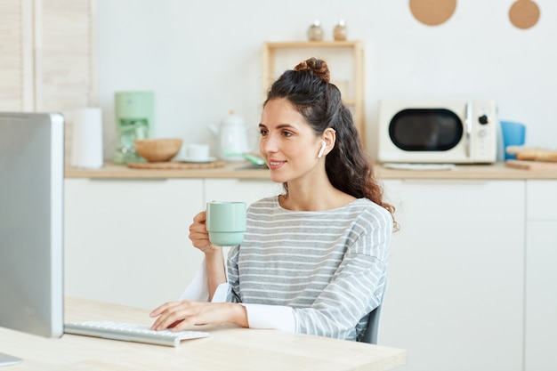 Horizontal medium portrait of young woman using her desktop computer and drinking morning coffee at home