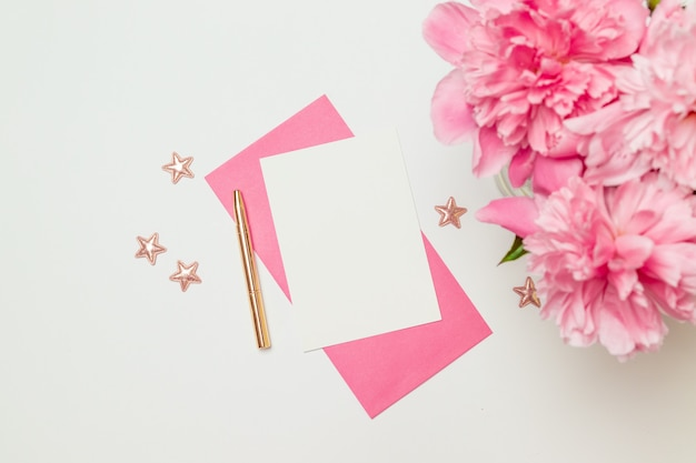 Horizontal minimalist card mockup with flower, craft envelope, blossom, flat lay, top view