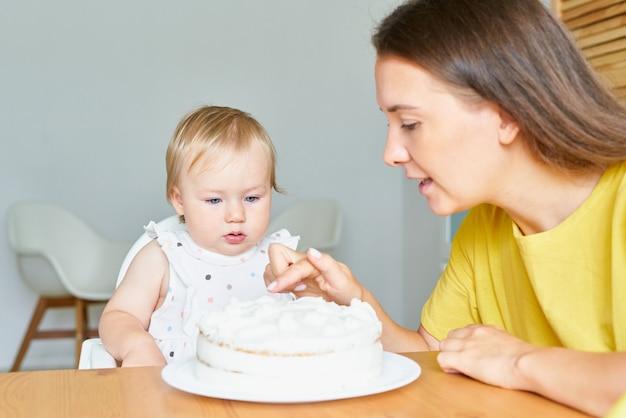 Очаровательная маленькая девочка смотрит на мать, дегустируя сливочный торт на день рождения