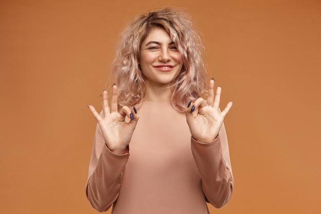 キュートでチャーミングなスタイリッシュな若い白人女性の横長は、嬉しそうに笑って、身振りで示して、大丈夫な兆候を示して、彼女の親指と前指を接続します