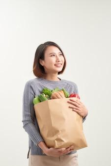 野菜があふれている紙袋を持っている女性の水平方向のカラー画像/あなたの食事療法に野菜を追加する