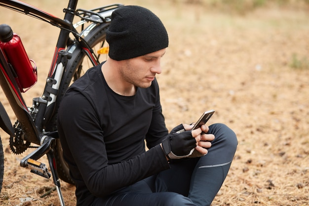Horizontal outdoor picture of young persistent sportsman sitting near his bicycle in forest, typing messages, using his phone, looking at its screen attentively, wearing black uniform for sport.