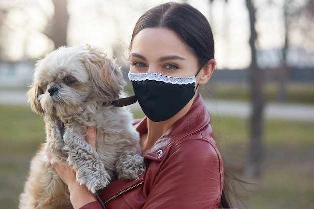 Horizontal outdoor shot of good looking careful brunette in mask being outside during quarantine, having walk with favourite pet, holding dog in hands. stay home concept.