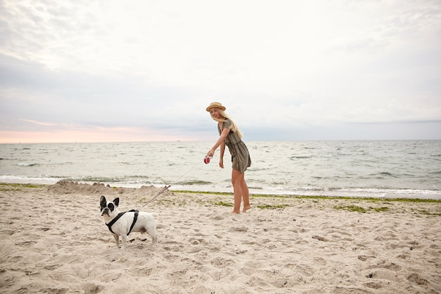 Horizontal outdoor shot of pretty young woman with blonde hair walking along beach on overcast with her dog, wearing summer dress and straw hat