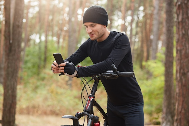 Horizontal outdoor shot of sportsman posing around nature with his bicycle, holding his mobile phone, touching its screen, using social networking sites, having short break.
