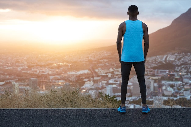 Horizontal panoramic view of thoughtful sportsman in sportclothes stands back, admires majestic mountain landscape and sunrise, stand on asphalt high above, big city in foreground.
