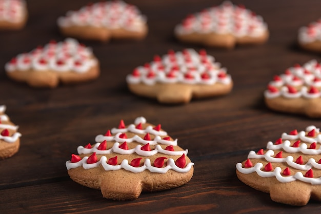 Horizontal pattern with cookies shaped christmas tree on a dark wooden background