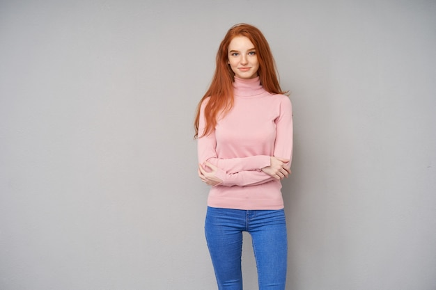 Foto orizzontale di bella signora dai capelli lunghi rossa vestita in maglione lavorato a maglia rosa e jeans in piedi sopra il muro grigio, tenendo le mani giunte sul petto e sorridendo positivamente