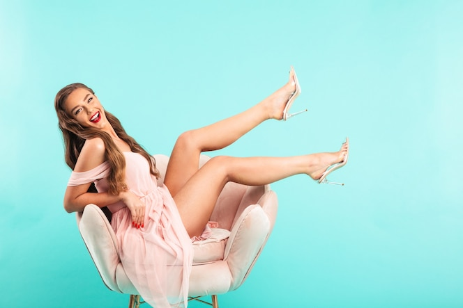 Horizontal photo of beautiful woman 20s in pink dress sitting in soft armchair showing long healthy legs without shoes, isolated over blue wall
