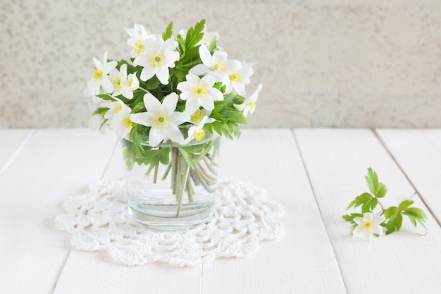 Horizontal photo of a bunch of white spring flowers in a glass