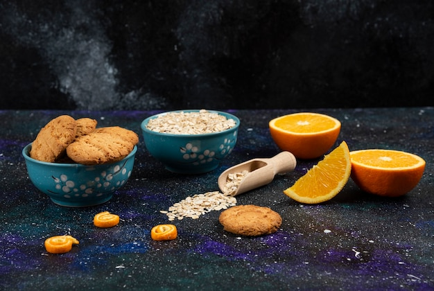 Horizontal photo of cookies and oatmeal in bowls, half cut and sliced orang eon ground.