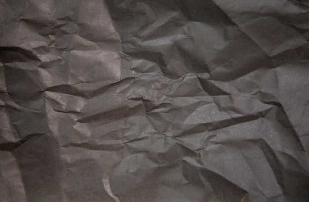 Horizontal photo of crumpled black paper for background.