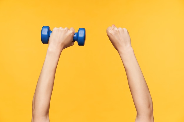 Horizontal photo of fair-skinned strong female raised hands making workout for muscules with blue dumbbell while posing against yellow background