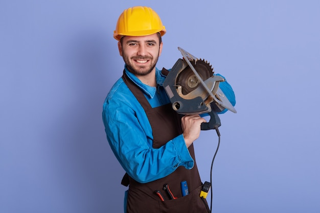 Horizontal photo of good looking handsome happy worker holding tool in both hands, looking directly at camera, smiling sincerely, wearing brown apron, blue overall and yellow helmet. work concept.