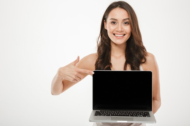 Horizontal photo of happy woman 30s smiling and demonstrating black empty screen of silver laptop on camera with finger, over white wall