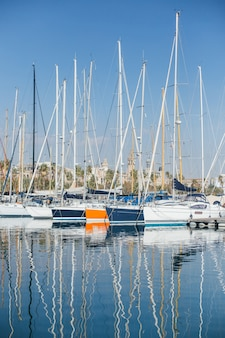 Horizontal photo of luxury and glamorous yachts and sailboats docked or parked in marina port in barcelona, spain