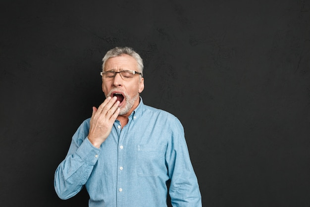 Horizontal photo of mature unshaved man 60s with grey hair wearing eyeglasses being sleepy and yawning because of insomnia, isolated over black wall