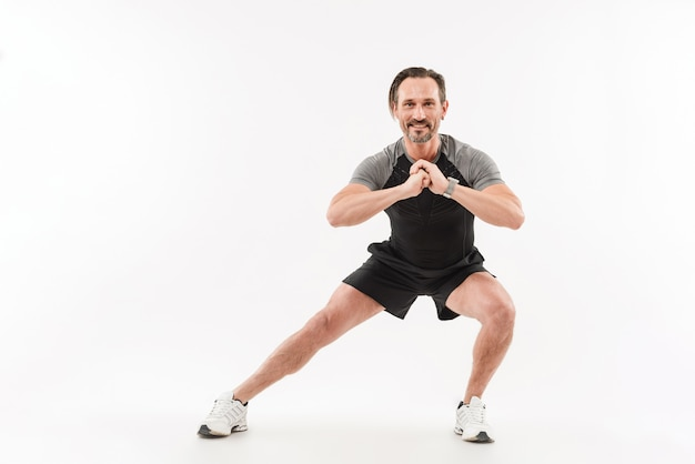 Horizontal photo of muscular man doing workout with stretching legs and sit-ups keeping hands in front of him