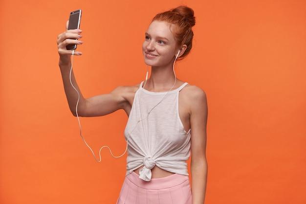 白いトップとピンクのスカートを着て、携帯電話で自分撮りをし、魅力的な笑顔でカメラを見て、セクシーなパンの髪型を持つ魅力的な若いリードヘッドの女性の水平方向の写真