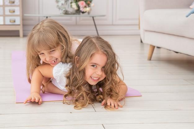Горизонтальное фото пары маленьких девочек играя на циновке йоги усмехаясь в живущей комнате, привычках здорового образа жизни и концепции образа жизни.