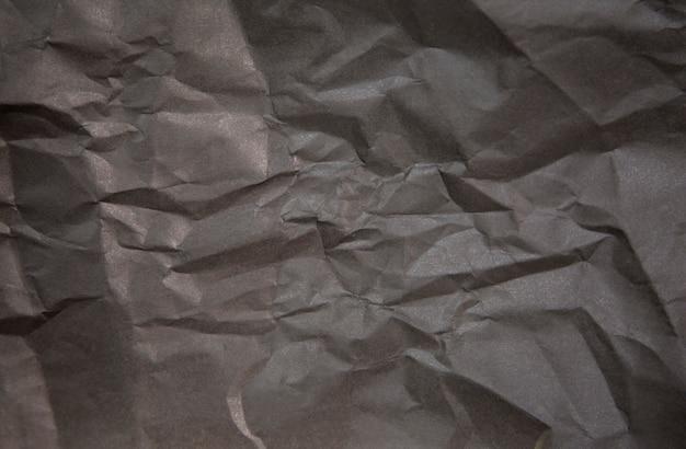 Горизонтальное фото мятой черной бумаги для фона.