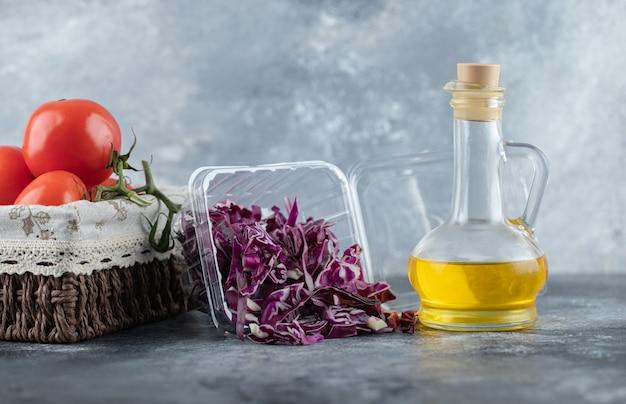 Горизонтальное фото свежих помидоров с нарезанной капустой и бутылкой масла на сером фоне.