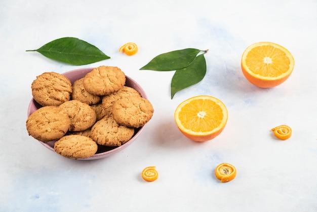 분홍색 그릇에 있는 집에서 만든 쿠키의 수평 사진과 흰색 표면 위에 오렌지를 반으로 자른다.