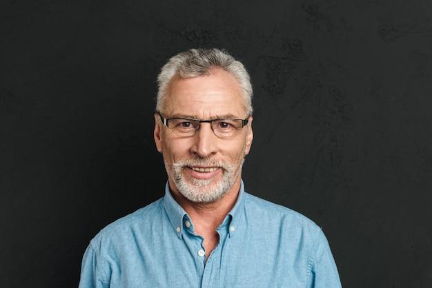 成熟した剃っていない男60年代の灰色の髪の笑顔の眼鏡と率直な視線、黒い壁に分離された水平の写真