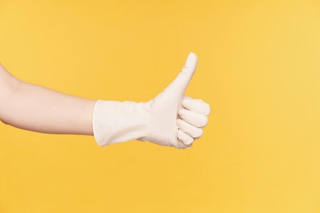 오렌지 배경 위에 절연 잘 한 기호를 보여주는 동안 엄지 손가락을 보여주는 흰 장갑에 제기 손의 가로 사진. 신체 언어 및 몸짓 개념