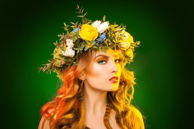 녹색 표면에 화 환을 가진 성적인 여자의 가로 사진