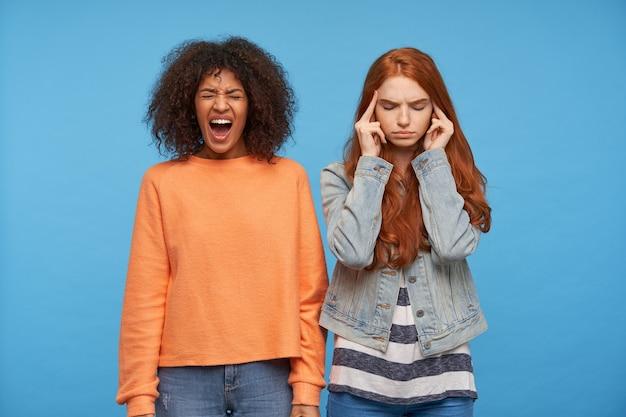 青い壁に立っている間、眉を眉をひそめ、目を閉じたままカジュアルな服を着たストレスのたまった若い魅力的な女性の水平方向の写真