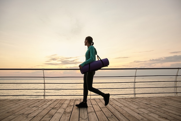 Горизонтальное фото гуляющей женщины на берегу моря утром, идущей на занятия йогой, которая делает утреннюю растяжку, держит фиолетовый коврик для йоги и смотрит в сторону.
