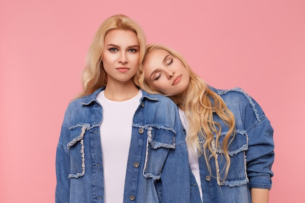 Горизонтальное фото молодых красивых длинноволосых белокурых сестер с кудрями в джинсовых пальто и белых футболках, стоящих на розовом фоне с опущенными руками