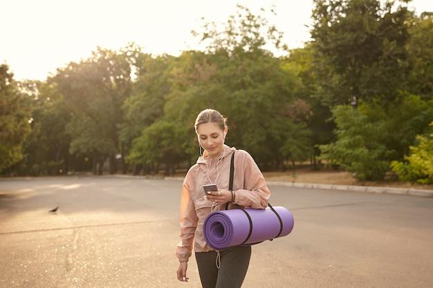 Горизонтальное фото молодой милой леди, идущей после йоги в парке и болтающей с другом, сжимает смартфон в руке и с улыбкой смотрит на дисплей, слушая музыку в наушниках.