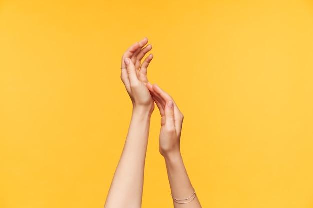 Горизонтальное фото молодых красивых рук женщины, нежно касаясь друг друга, будучи изолированными на желтом фоне. знаки тела и языковая концепция