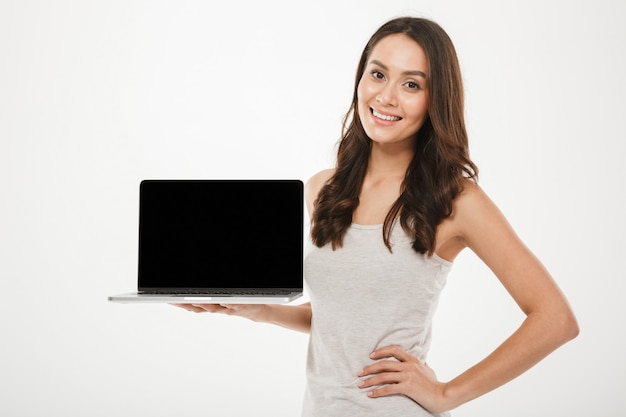 Horizontal photo of pleased educated woman smiling and demonstrating black empty screen of silver laptop holding on hand, over white wall