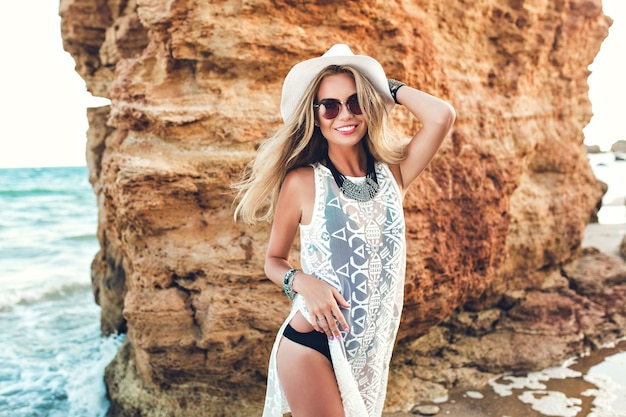 Foto orizzontale di bella ragazza bionda con i capelli lunghi in cappello in posa per la fotocamera sulla spiaggia rocciosa.