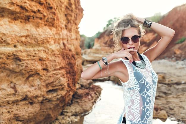Horizontal photo of pretty  blonde girl with long hair  posing to the camera on rocks background, she wears black bikini under white dress, sunglasses. she holds hair above.