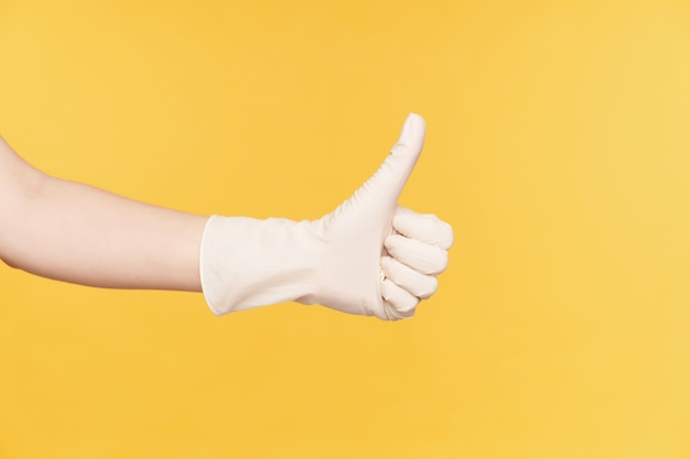 Horizontal photo of raised hand in white gloves showing thumb while demonstrating well done sign, isolated over orange background. body language and gesturing concept