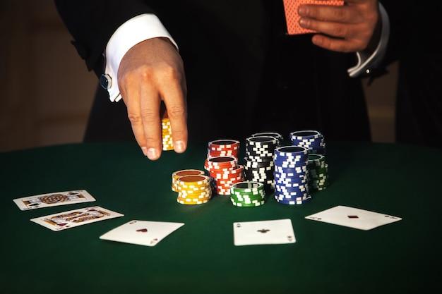 포커를 하는 남성의 얼굴이 없는 가로 사진. 도박과 카지노의 개념에 따라