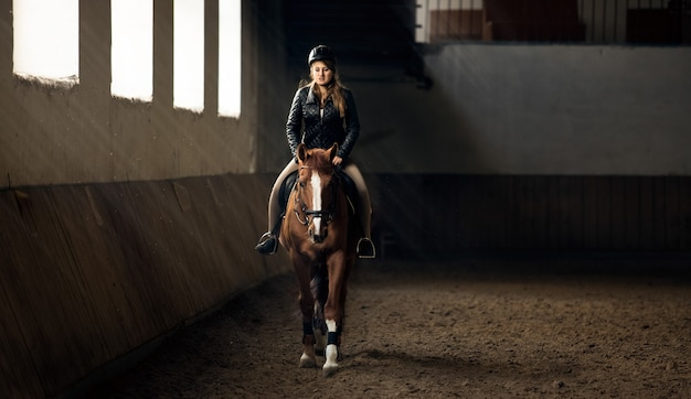 Horizontal photo of woman riding horse on manege in riding hall