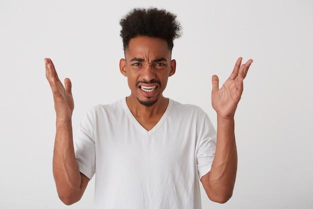 Foto orizzontale di giovane uomo barbuto dalla pelle scura attraente che fa smorfie il suo fronte e che solleva le mani