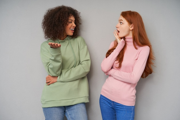 Horizontal photo of young attractive women having exciting conversation while posing over grey wall, raising emotionally their hands while sharing news