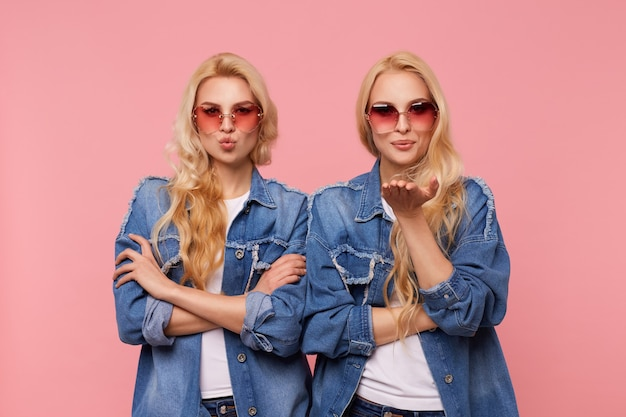 Horizontal photo of young beautiful long haired females with wavy hairstyle folding lips in air kiss while looking positively at camera, isolated over pink background