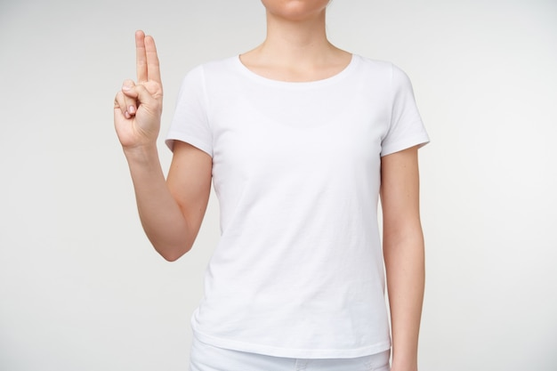 Horizontal photo of young female keeping two fingers together while showing letter u using death alphabet, isolated over white background in casual wear