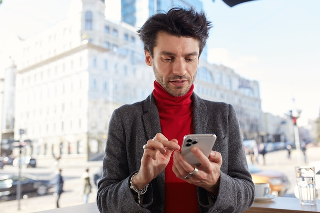Horizontal photo of young handsome dark haired man dressed in formal clothes typing message on his mobile phone while standing over urban background