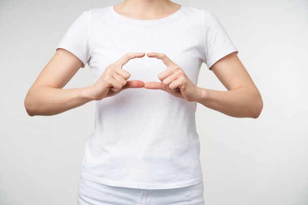 Horizontal photo of young woman learning sign language, making ellipse with her fingers while showing word school, isolated over white background